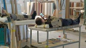 Os trabalhadores descansam e usam o telefone, resto no local de trabalho produção de portas interiores feitas da madeira filme