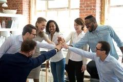 Os trabalhadores diversos excitados juntam-se às mãos na atividade teambuilding fotografia de stock royalty free