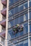 Os trabalhadores do arranha-céus com equipamento de escalada mudam a janela na construção alta fotografia de stock