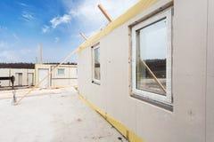 Os trabalhadores do construtor do Roofer com o guindaste que instala os painéis isolados estruturais SORVEM Casa energia-eficient Fotos de Stock
