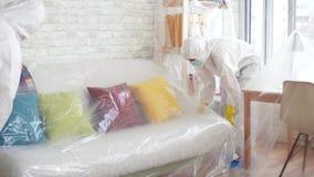Os trabalhadores em ternos protetores cobrem a mobília com a película de plástico