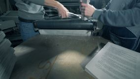 Os trabalhadores empilham o papel nas pilhas em uma facilidade da tipografia filme