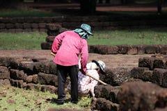 Os trabalhadores estão cancelando ervas daninhas que a grama para renova a área do local arqueológico na cidade antiga de Sri The imagens de stock royalty free