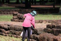 Os trabalhadores estão cancelando ervas daninhas que a grama para renova a área do local arqueológico na cidade antiga de Sri The imagem de stock