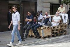 Os trabalhadores estão descansando no hora do almoço Os trabalhadores sentam-se no andaime e falam-se entre si Imagens de Stock