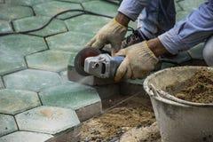 Os trabalhadores estão pavimentando assoalhos do tijolo imagem de stock