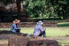 Os trabalhadores estão sentando a ruptura das ervas daninhas que claras a grama para renova a área do local arqueológico na cidad foto de stock