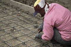 Os trabalhadores fêmeas estão ligando a estrutura do fio de aço fotografia de stock royalty free