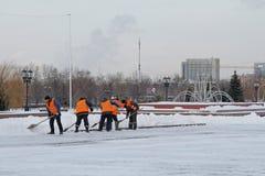Os trabalhadores limpam a neve dos passeios no monte de Poklonnaya em Moscou fotografia de stock