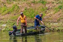 os trabalhadores limpam o rio de uma maca diferente Fotos de Stock Royalty Free