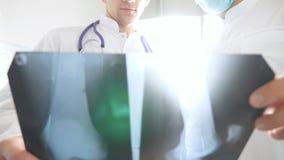 Os trabalhadores médicos no escritório do hospital examinam cópias do raio X Os médicos masculinos consultam um com o otro ao olh video estoque