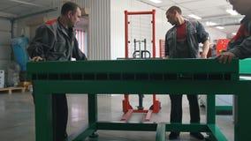 Os trabalhadores masculinos montam máquinas do CNC na fabricação video estoque