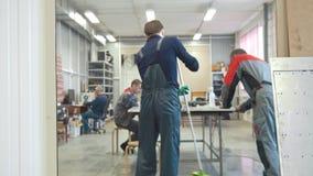Os trabalhadores masculinos na fabricação do CNC fazem à máquina a limpeza do espaço de trabalho video estoque