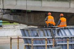 Os trabalhadores montam a estrutura da ponte e dos povos sentados para baixo ao resto imagens de stock royalty free