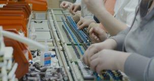 Os trabalhadores montam manualmente partes eletrônicas no PWB vídeos de arquivo