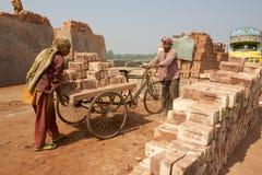 Os trabalhadores movem tijolos em uma fábrica em Dhaka, Bangladesh foto de stock royalty free