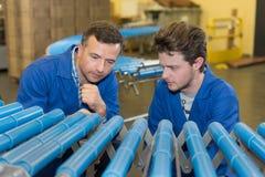 Os trabalhadores no plástico conduzem a fábrica fotografia de stock royalty free