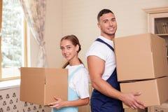 Os trabalhadores novos alegres estão limpando uma casa com Fotos de Stock Royalty Free