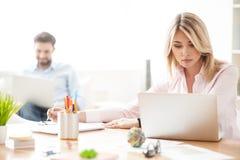 Os trabalhadores novos alegres estão usando computadores Fotos de Stock