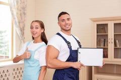 Os trabalhadores novos atrativos no avental são limpar Foto de Stock Royalty Free