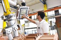 Os trabalhadores novos da engenharia mecânica operam uma máquina para o windi Imagens de Stock