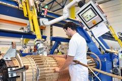 Os trabalhadores novos da engenharia mecânica operam uma máquina para o windi Fotografia de Stock Royalty Free