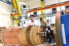 Os trabalhadores novos da engenharia mecânica operam uma máquina para o windi Foto de Stock