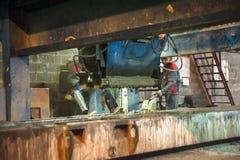 Os trabalhadores operam a máquina na fatura das placas Fotografia de Stock