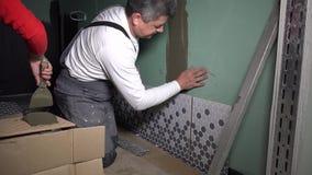 Os trabalhadores profissionais instalam telhas colocadas na parede do banheiro filme