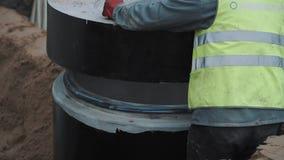 Os trabalhadores puseram o anel concreto da câmara de visita sobre a estrutura do esgoto no terreno de construção filme
