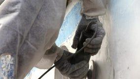 Os trabalhadores rasgam fora a pintura no metal no processo dos reparos no estaleiro video estoque