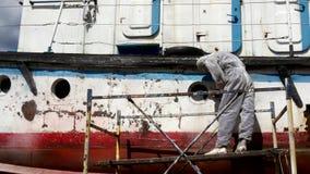 Os trabalhadores rasgam fora a pintura no processo dos reparos de embarcação do mar do rio no estaleiro vídeos de arquivo
