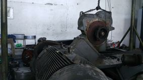 Os trabalhadores reparam da maquinaria industrial que está experimentando dano severo Reparo dos motores do compressor imagem de stock royalty free