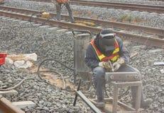 Os trabalhadores reparam a estrada de ferro com limpado com jato de areia. Imagem de Stock