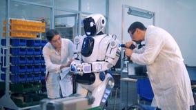 Os trabalhadores reparam um robô em uma sala do laboratório filme