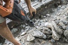Os trabalhadores usam o disjuntor concreto bonde Trabalhador masculino que repara a superfície da entrada de automóveis com jackh foto de stock