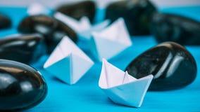 Os trabalhos de equipa do Livro Branco enviam entre pedras abstratas da rocha no fundo azul Fotografia de Stock Royalty Free