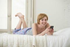 Os trabalhos em rede vermelhos atrativos novos do Internet da mulher do cabelo com o telefone celular que encontra-se na cama no  Fotos de Stock Royalty Free