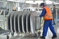 Os transportes do trabalhador no carro do detalhe do corpo de carro Loja do a Imagens de Stock
