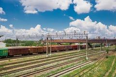 Os trens com bens e carros de frete estão na estrada de ferro fotografia de stock