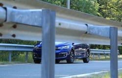 Os trilhos da estrada cercaram a estrada asfaltada e o sedan azul na estrada Foto de Stock