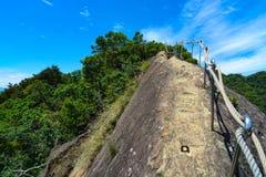 Os trilhos de mão da corda que seguem um trajeto de caminhada ao longo de um cume trecherous da montanha no Wu Liao Jian arrastam Fotografia de Stock Royalty Free