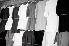 Os Tshirts penduram na loja ou no mercado local de castries, stlucia Roupa colorida na venda Venda, compra e compra preto foto de stock