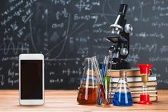 Os tubos com líquidos químicos estão em uma tabela de madeira em um chalkbo fotos de stock