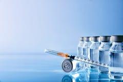 Os tubos de ensaio agrupam e seringa na tabela com fundo azul Fotografia de Stock Royalty Free