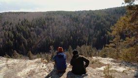 Os turistas acoplam o assento em uma rocha que olha as aventuras coníferas da floresta longe da casa no por do sol video estoque