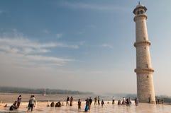 Os turistas admiram um dos minaretes de Taj Mahal Imagem de Stock Royalty Free