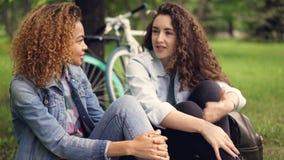 Os turistas alegres das jovens mulheres são de conversa e de riso o assento no gramado no parque após o dia ativo em bicicletas P filme