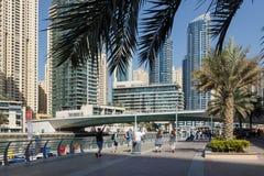 Os turistas andam ao longo do passeio no distrito do porto de Dubai em um dia ensolarado fotos de stock