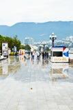 Os turistas andam na terraplenagem em Yalta na chuva Fotografia de Stock